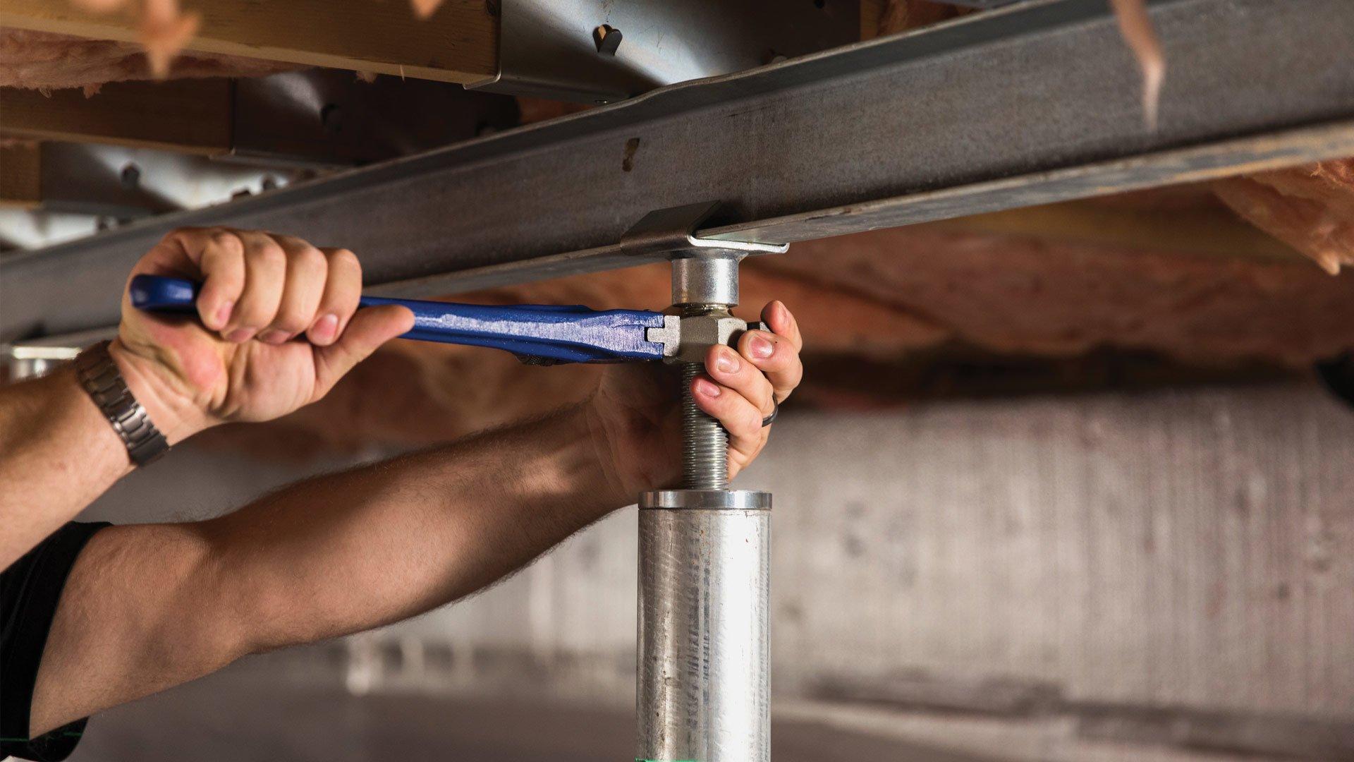 Technician using tool to tighten bracket