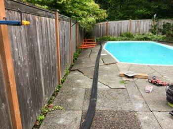 Cracked pool deck before repaired