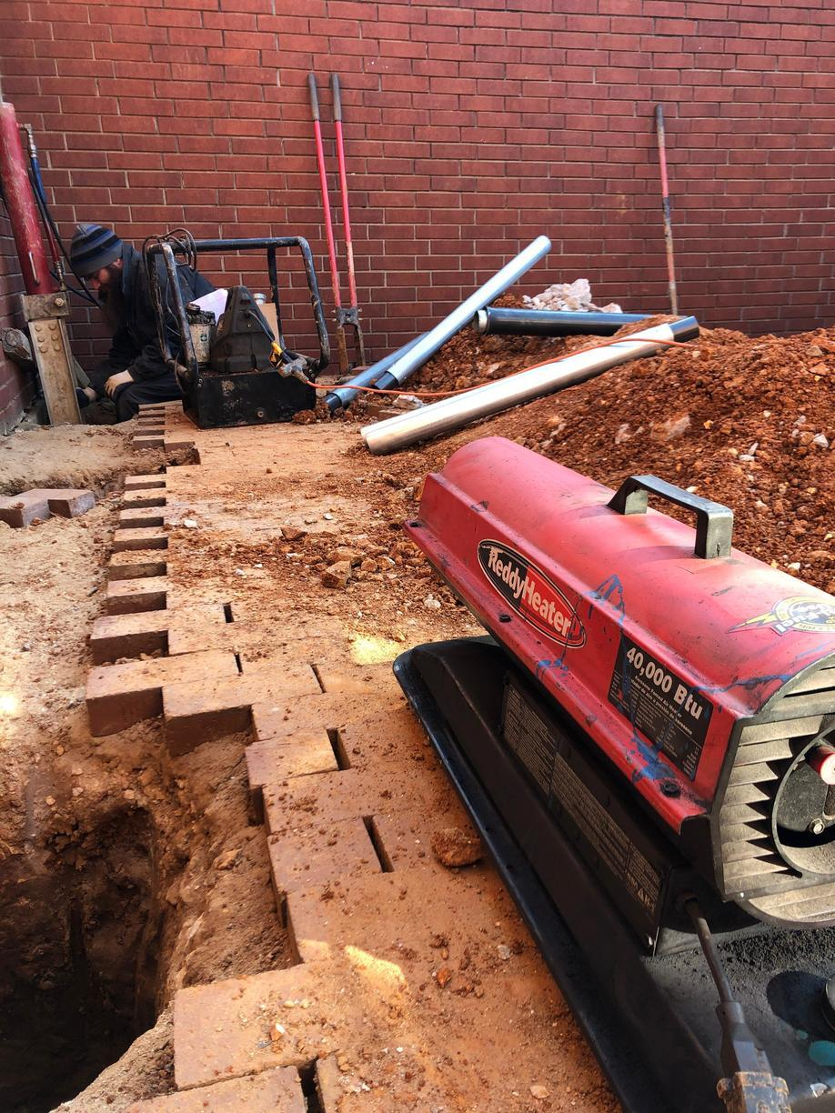 The soil along the foundations edge are removed to install hydraulic driven piers to load bearing soil. This is a picture of Eric working hard to keep piers driving as well as keeping warm!