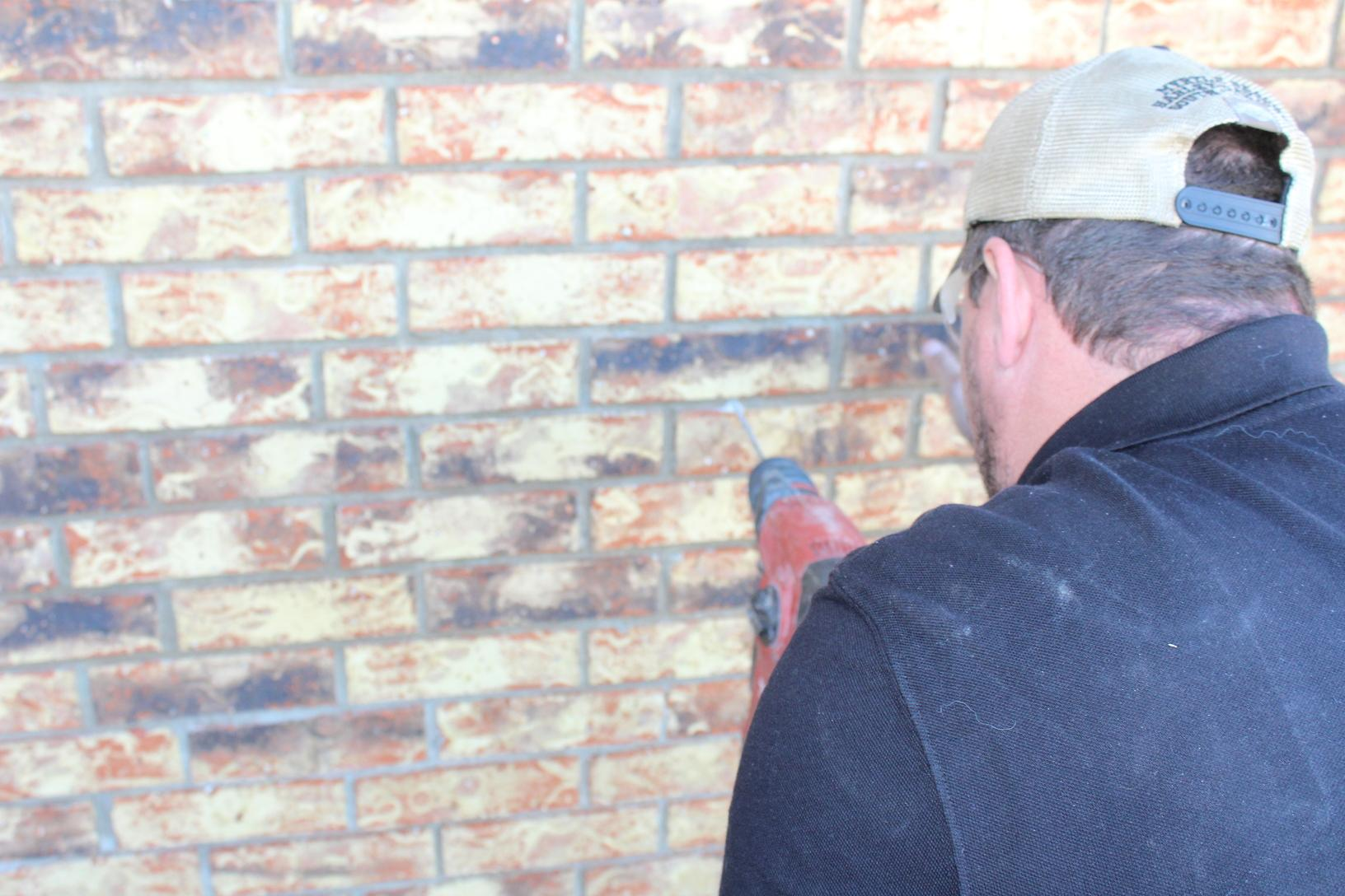 To grip two bricks at a time, the anchors are cored through the mortar lines.