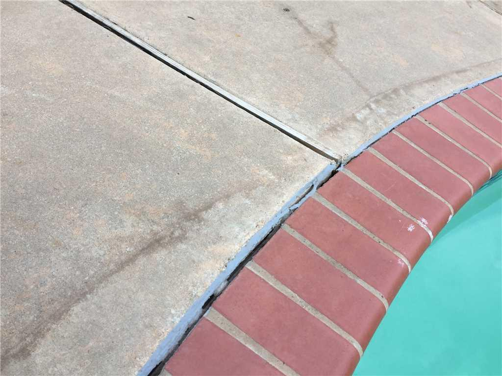 The Urethanesealer around the pool edge has become loose and deteriorated in the hot sun.