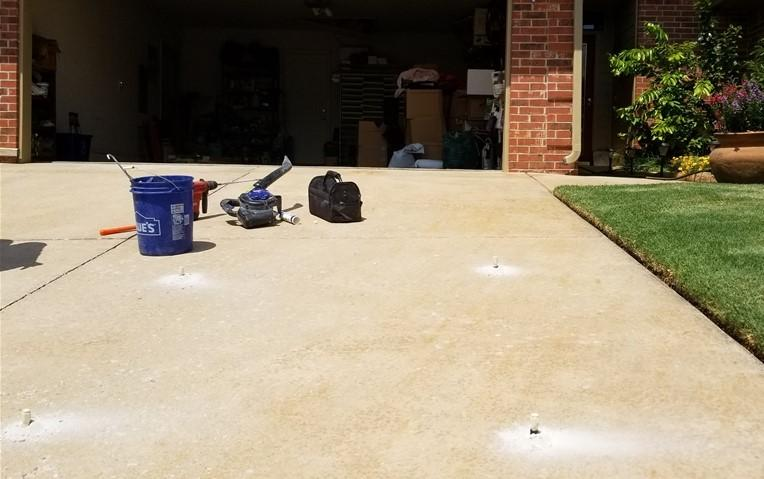 The driveway is protected by installing POLY Level ports every few feet. Then the injection fills voids beneath the slab.