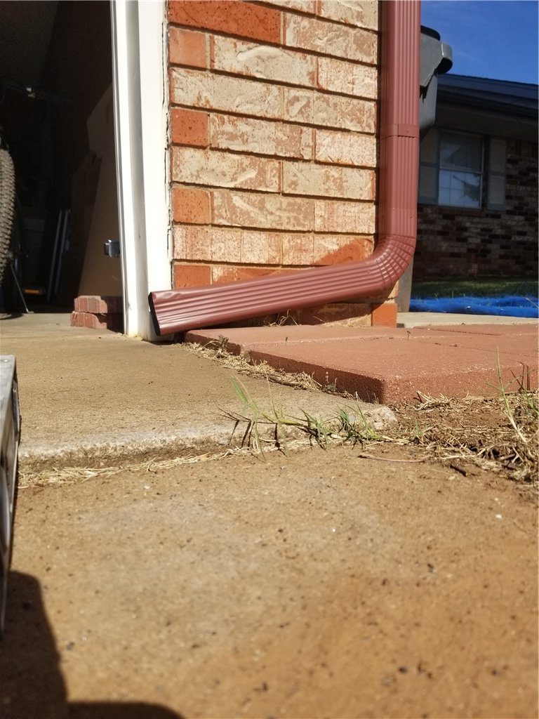 Many times the concrete settles because of downspout lines discharging directly on top of the driveway slab. This water runs down the joints and erodes the soil from under the driveway causing settling.