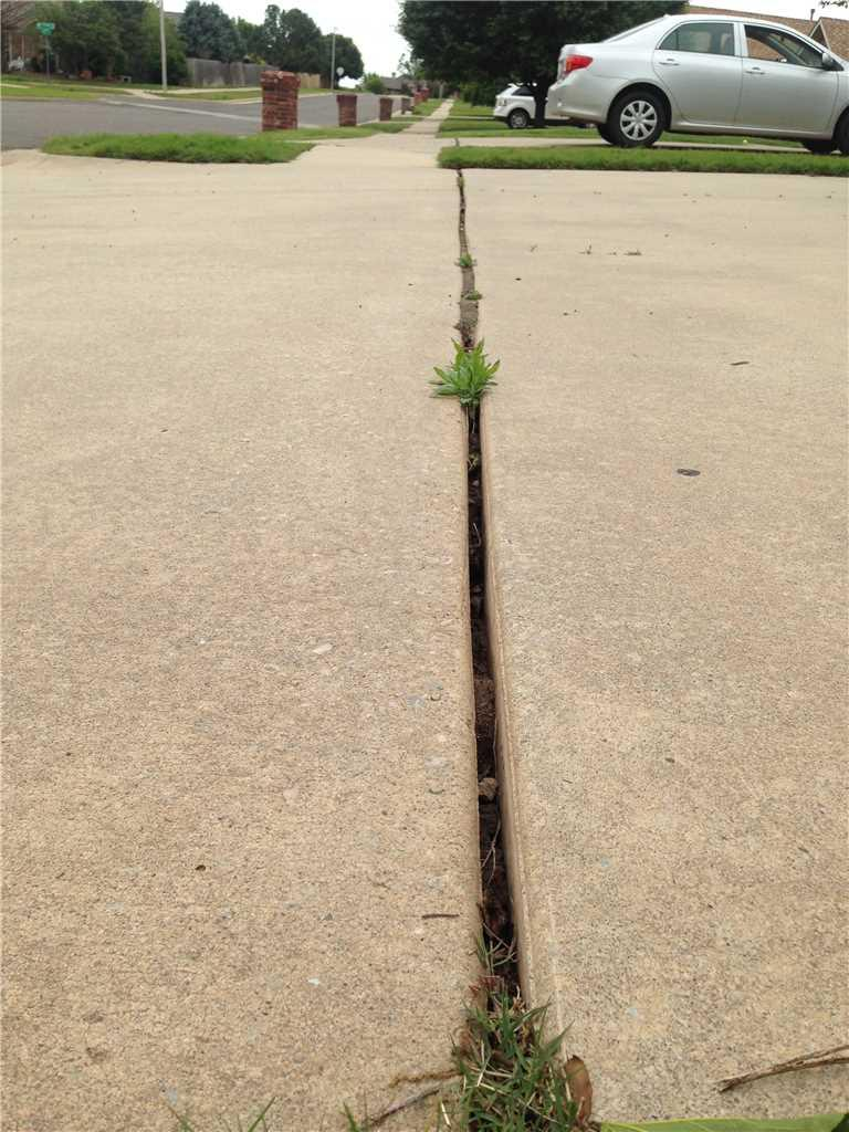 The old expansion joint installed by the developer has long since deteriorated. Now this leaves a space for grass to grow and weeds to develop.