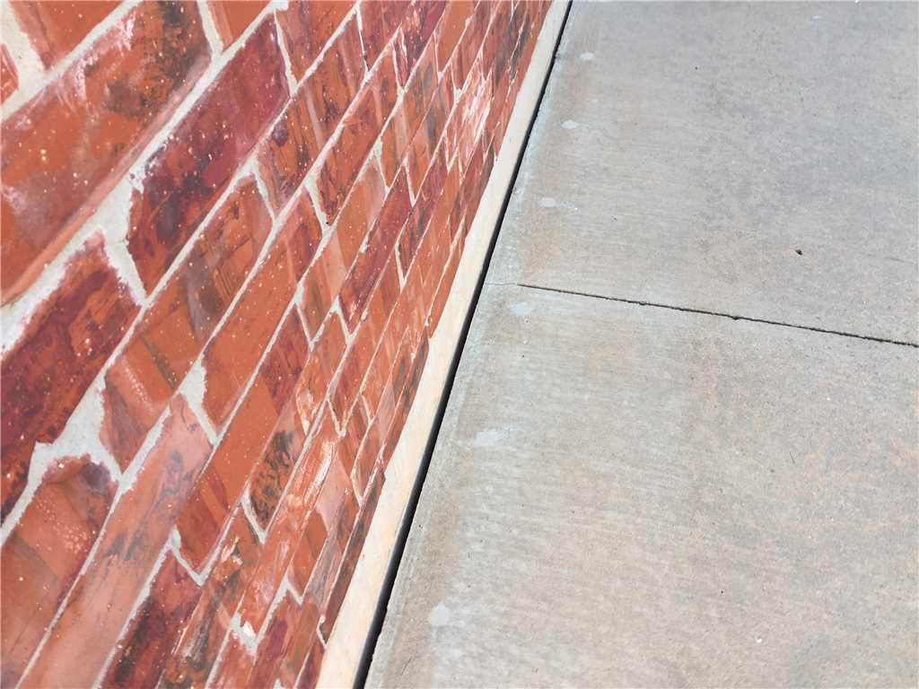 This expansion joint allowed water and debris to leverage between the home and the wall.