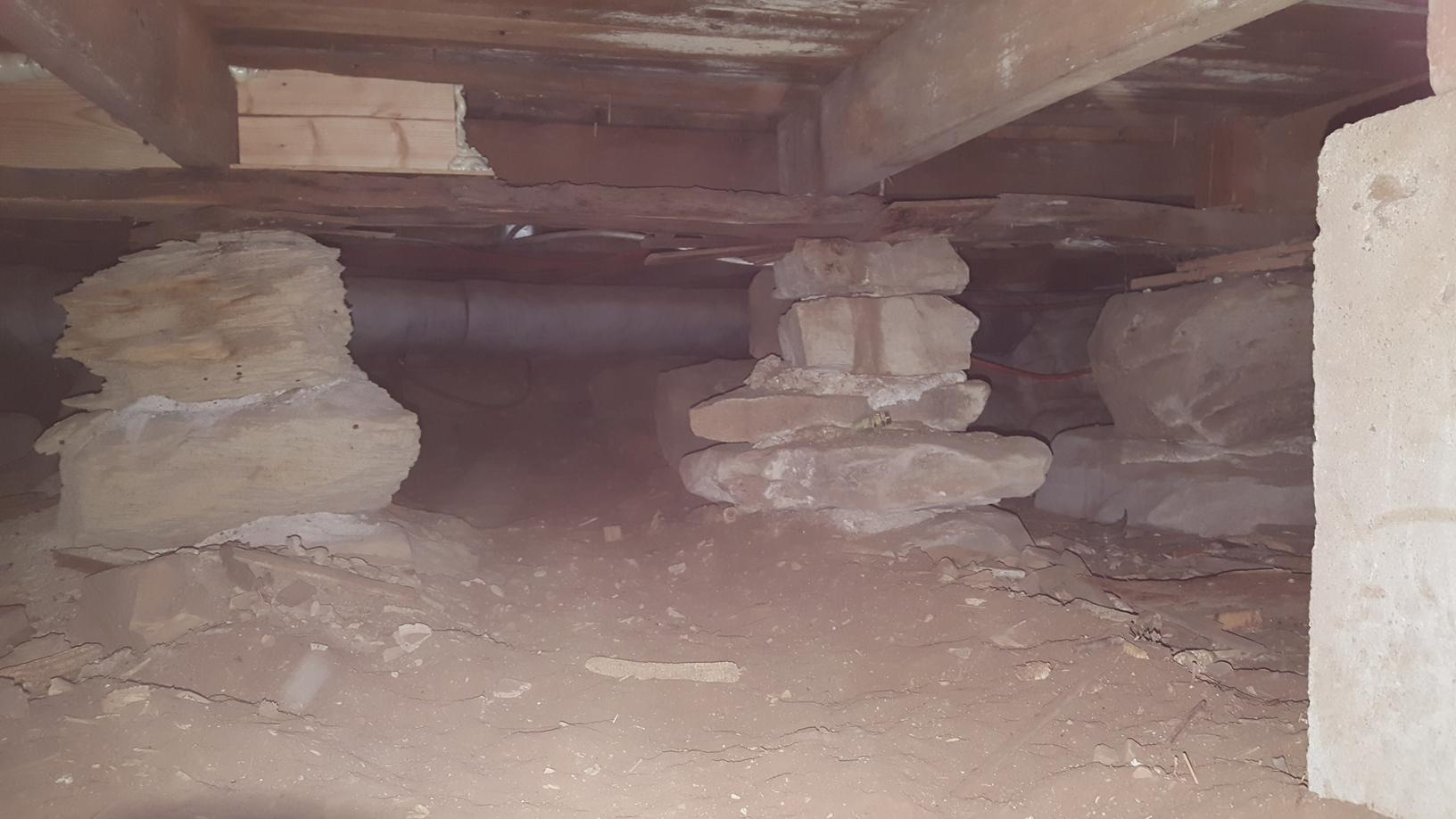 The original wall of the home was constructed of old rock piers and the framing rested directly on the top without support.