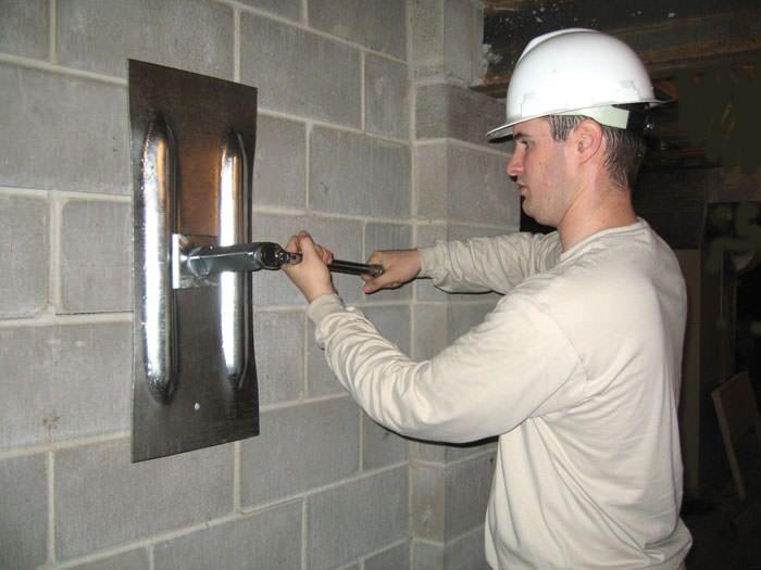 Vest Foundation technician tighten wall anchor