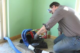Production leader, Adam Blake installing PolyLevel with protective gear and cover to protect finished areas.